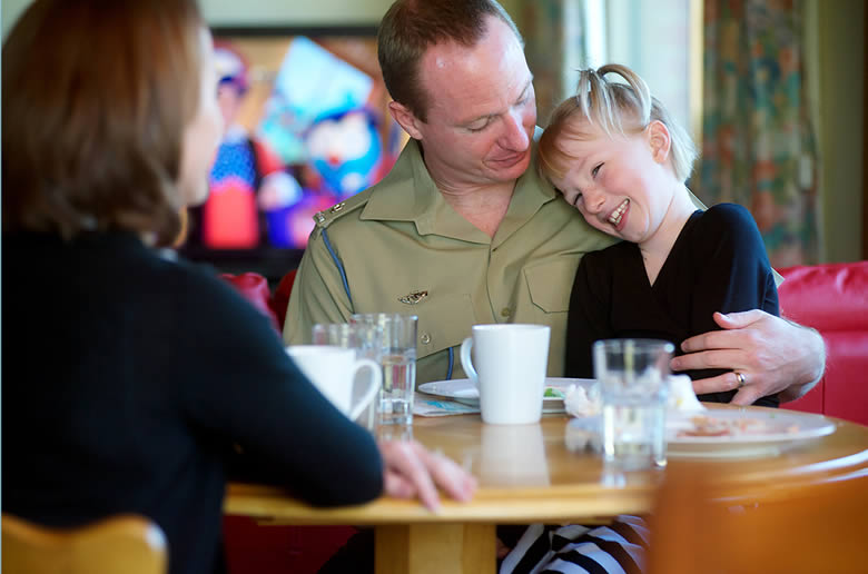 A veteran's family having a meal in the public space. An army officer cuddles a child.