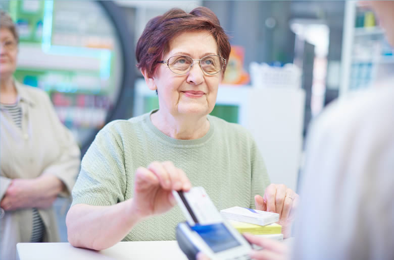 An older female presenting the Veteran Card at the cash register.